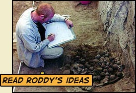 """read roddy's ideas"" - roddy squating and drawing a exposed group of clay balls"