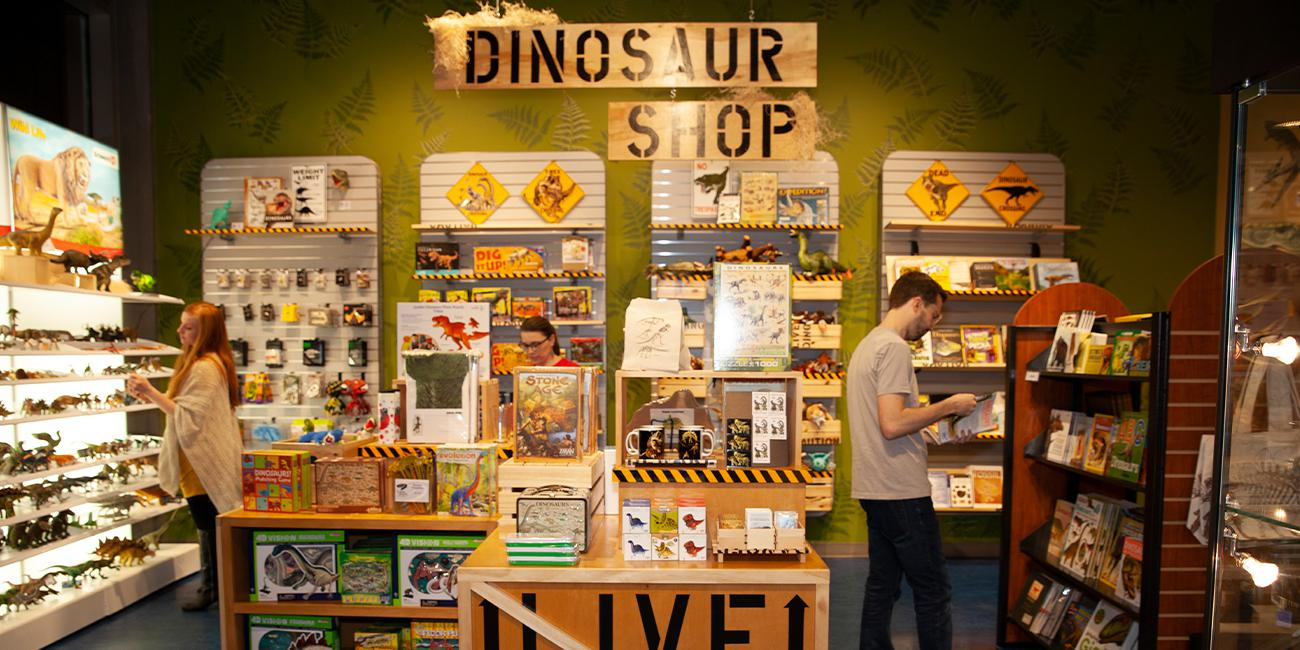 Explore Store Gift Shop featuring people shopping for dinosaur gear like shirts and fake fossils.