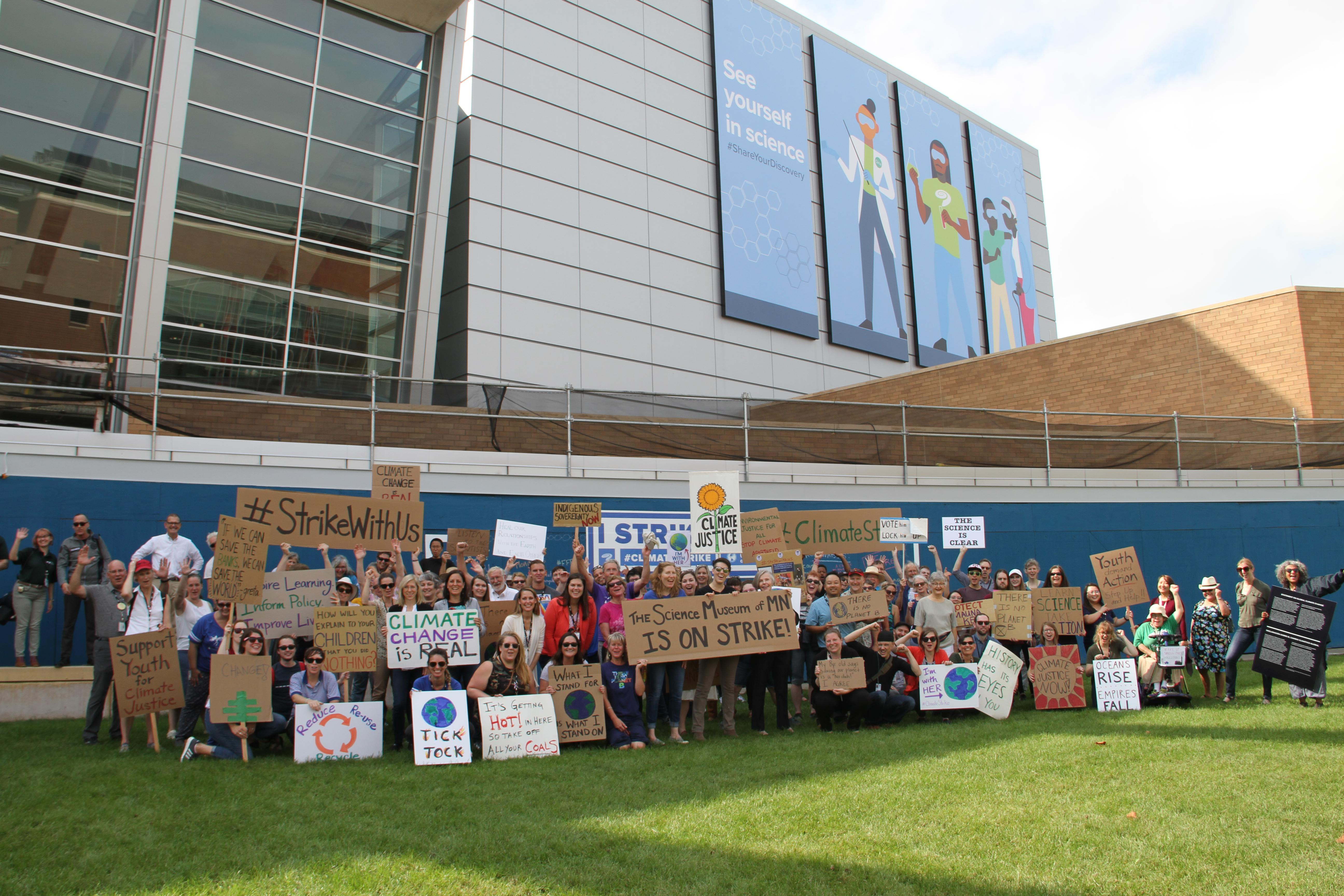 Group photo of Science Museum staff holding signs, participating in the climate strike.