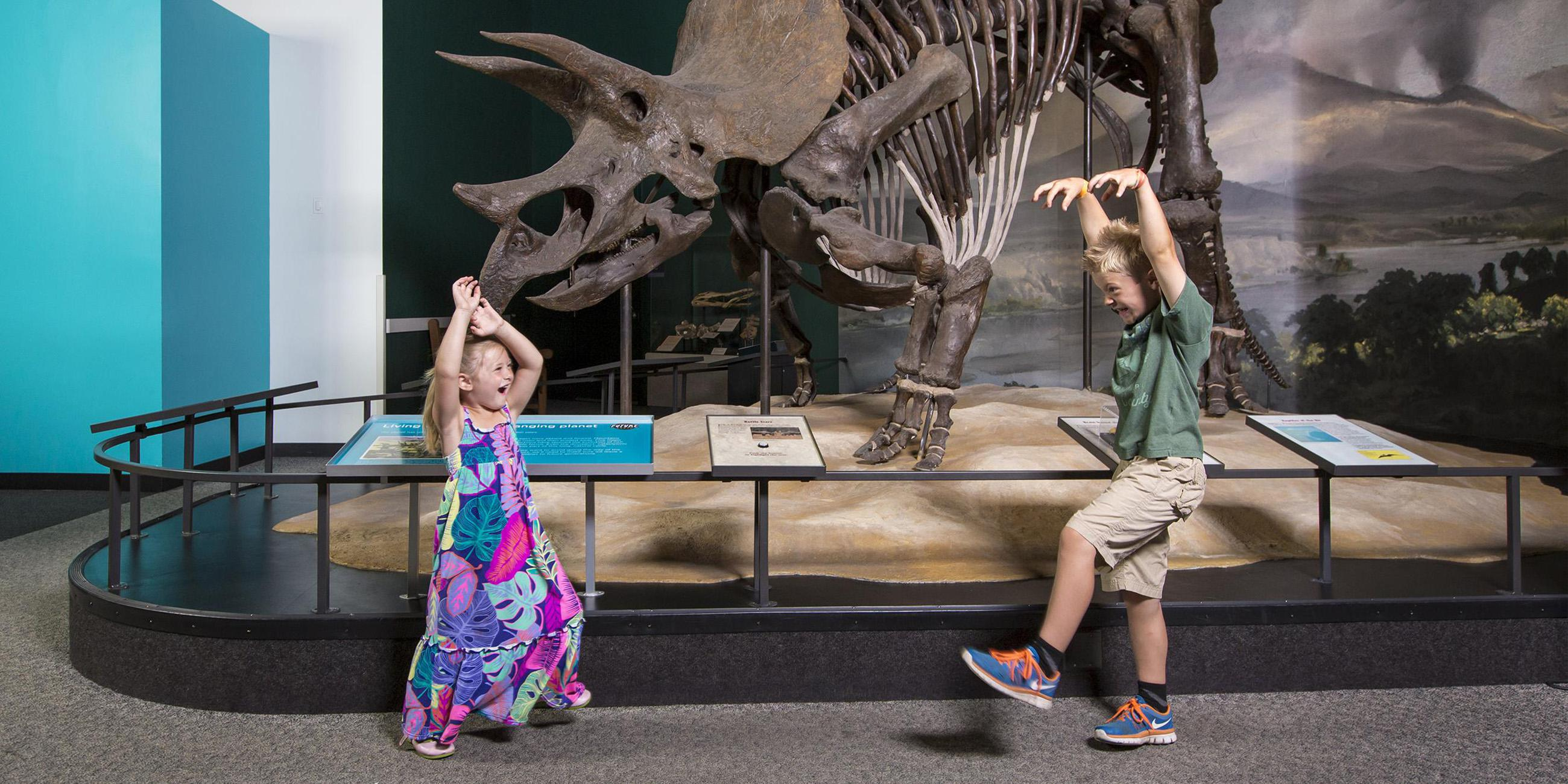 Two children playing in the Dinosaur gallery.