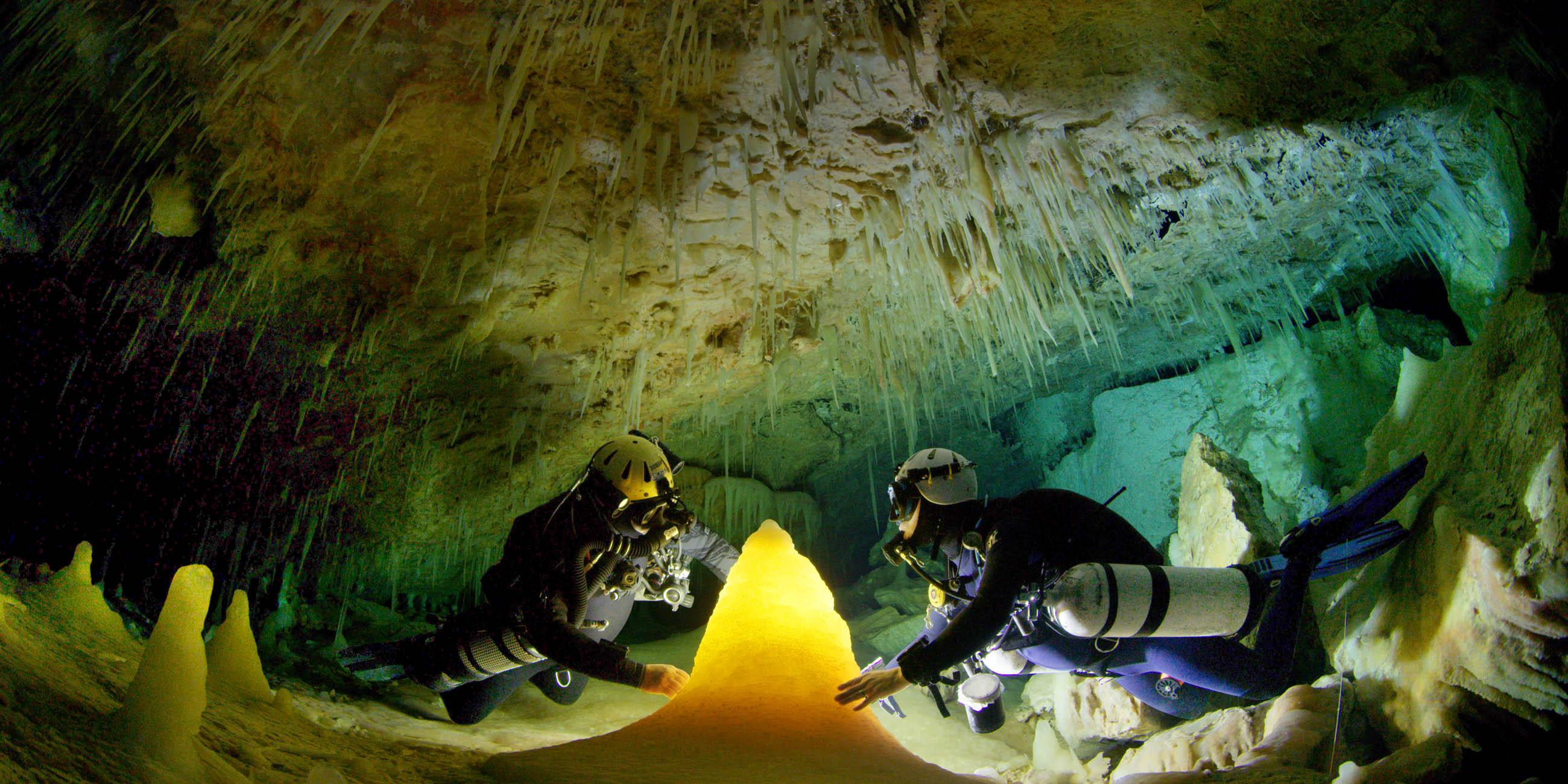 Underwater Cave with Divers Illuminating a Stalagmite