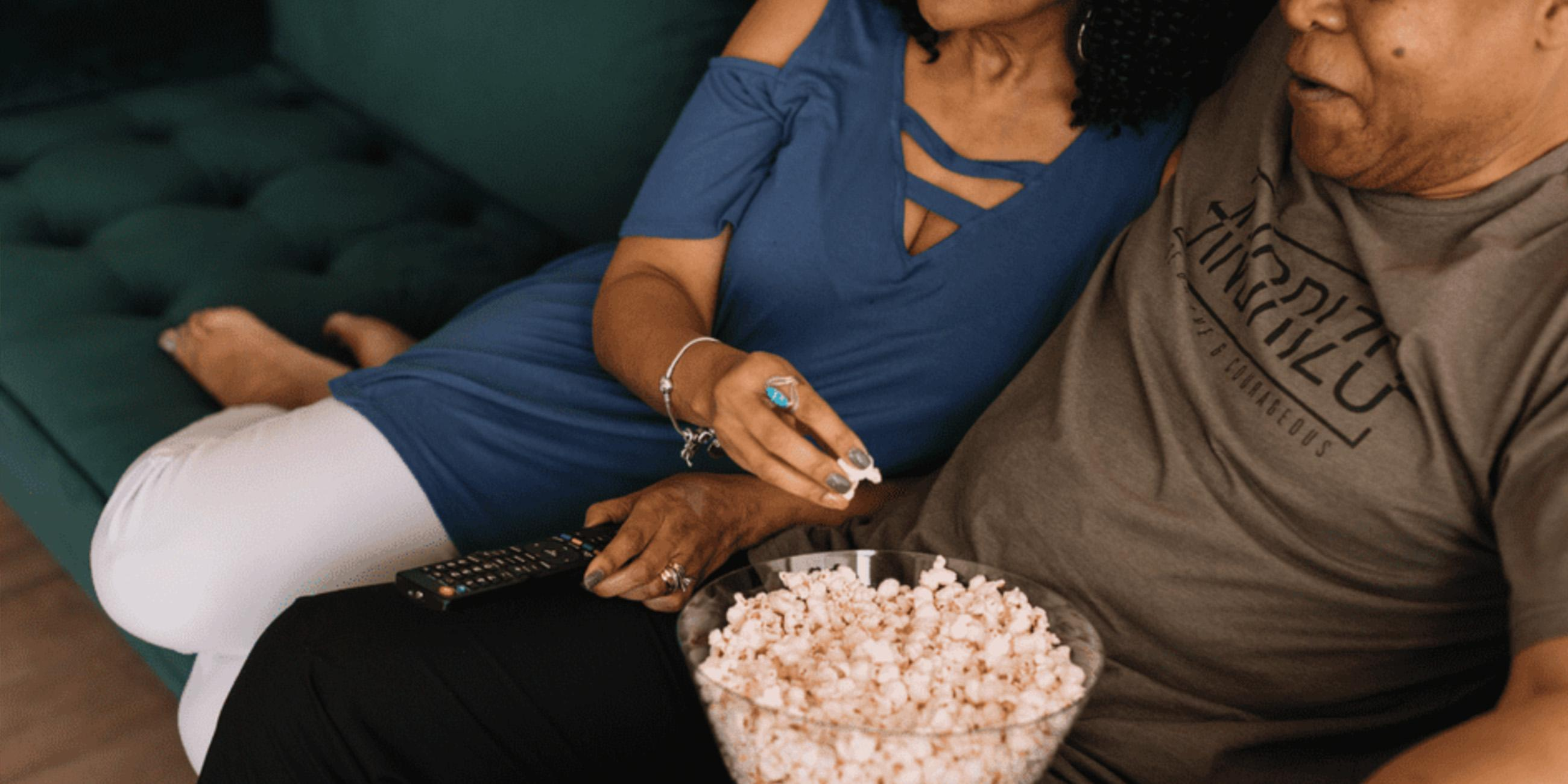 A couple eating popcorn at home.