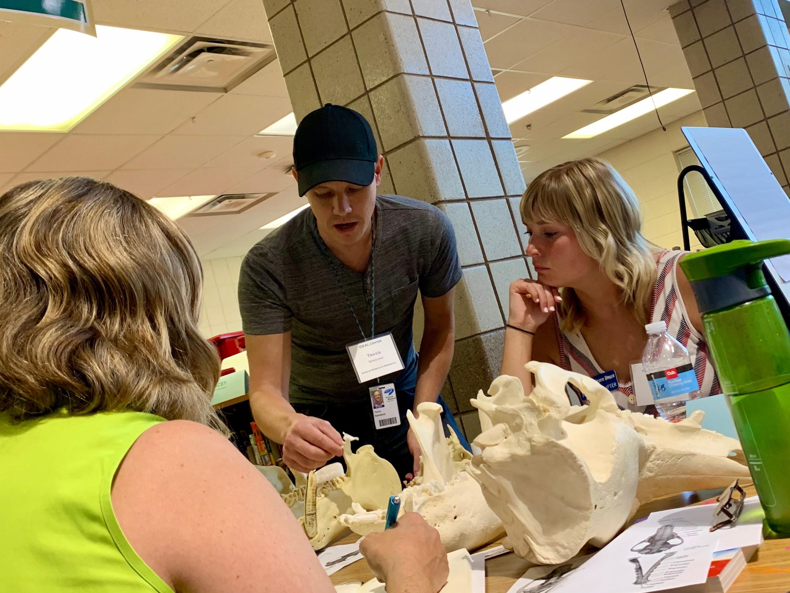 An IDEAL Center instructor leading a discussion at a table featuring bones with two other people.