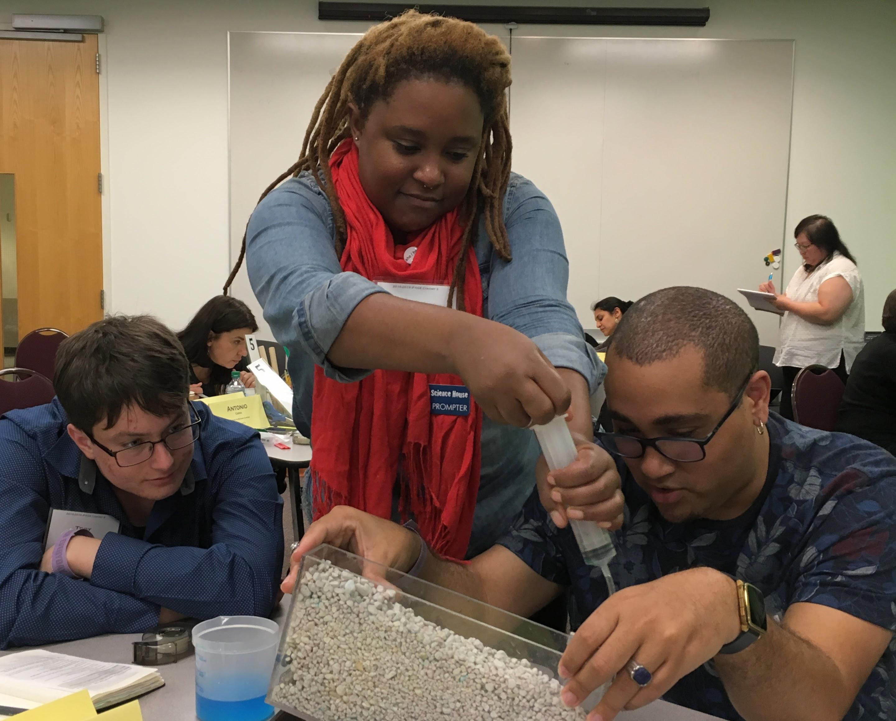 A group of three going a research experiment by injecting liquid into a container filled with rocks.