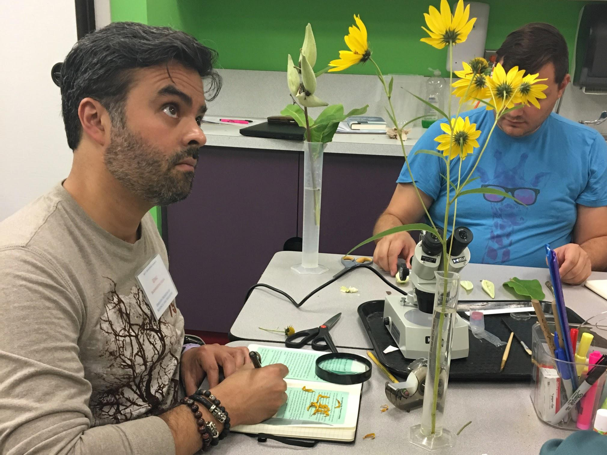 A person looking at a flower, making notes.