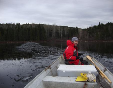 Breaking ice to sample sediment on a lake in the Réserve Faunique des Laurentides in Québec, Canada.