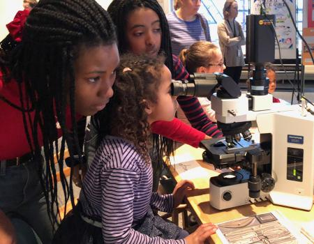 Two young women help a girl look through a microscope.