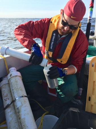 Adam Heathcote collects a suspended sediment sample from a buoy station on Lake of the Woods.