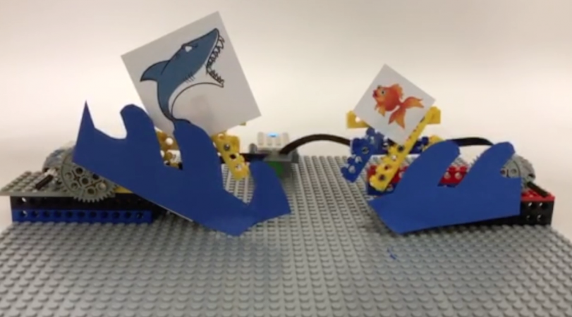 A picture of a lego contraption with a shark and a fish on it