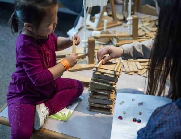 A young girl creates a structure using wooden blocks.