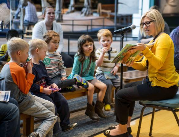 A woman reads a book to an engaged group of kids at the Science Live Theater.