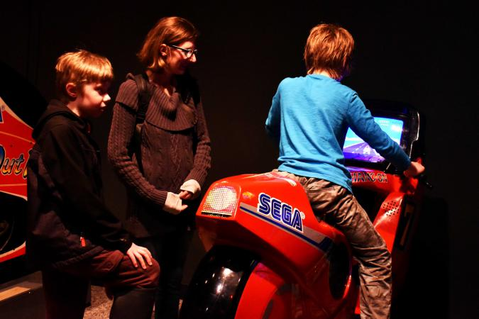 A child races on a motorcycle video game while his family watches.