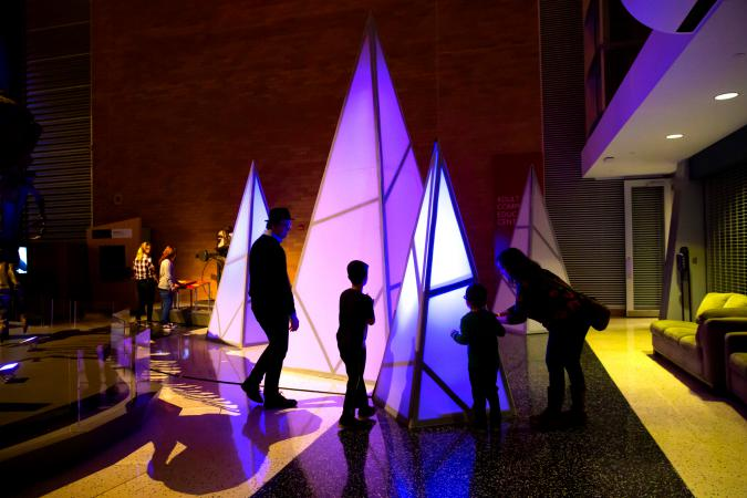 A family enjoying the interactive shards in the Museum lobby during Illumination.
