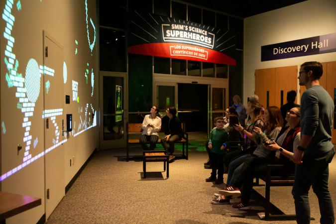 Patrons playing the giant video game near the new Science Superhero's exhibit.