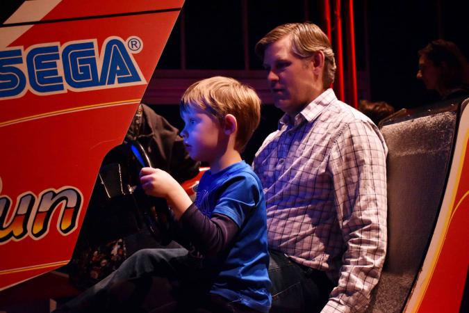 A family plays a car racing game.