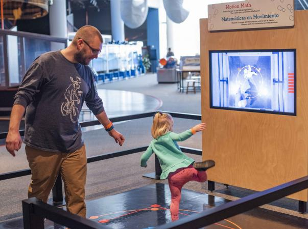 A child and their guardian play in the Math Moves exhibit.