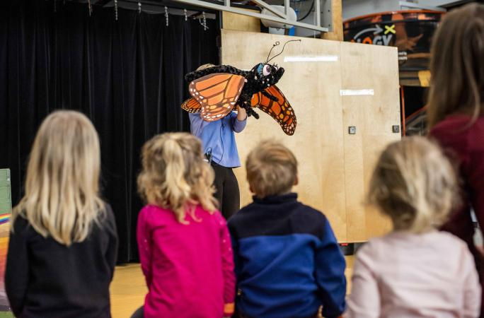 A group of children watch a Science Live show featuring a butterfly.