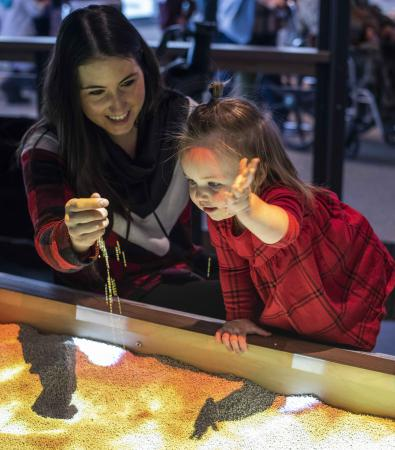 A child with their guardian playing with the 3D topographic table map in the museum.